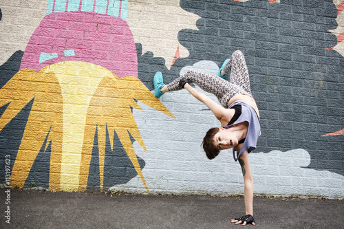 Graffiti New York State,Woman doing handstand in front of graffiti wall