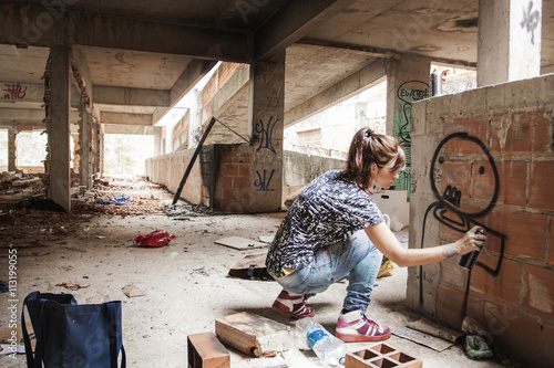 Woman spraying graffiti on building wall Poster