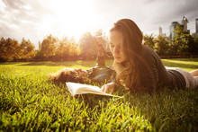 Two Young Women Reading In Par...