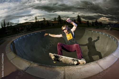 Plakat Skater doing trick on rim of bowl