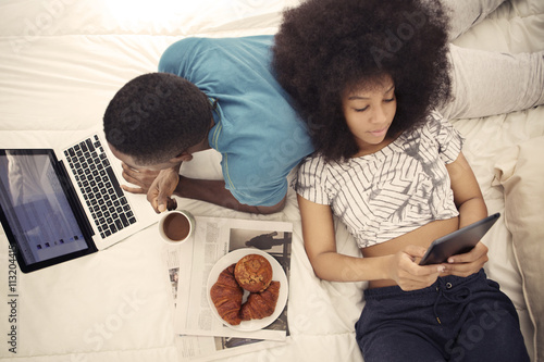 Couple having croissants and using technology while resting on bed at home