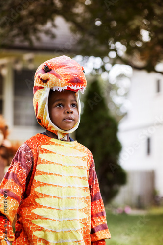 Cute boy wearing dinosaur costume standing in yard during Halloween