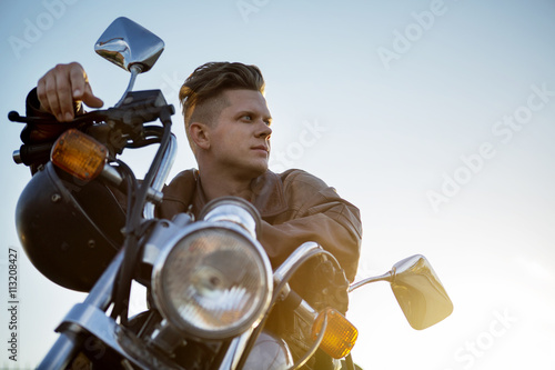 Low angle view of man sitting on motorcycle against clear sky Poster