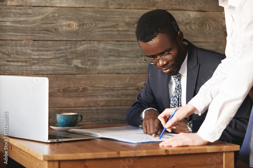 Fotografía  Focused African American businessman checking papers with his personal assistant in white shirt