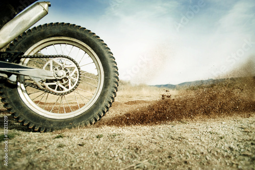 Cropped image of motorcycle on dirt road Poster