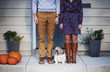 Young couple standing on porch of house with small dog