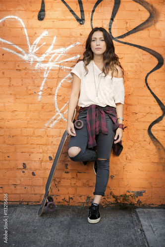 Graffiti Young female posing with skateboard against brick wall with graffiti