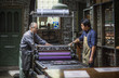Two workers at printing press
