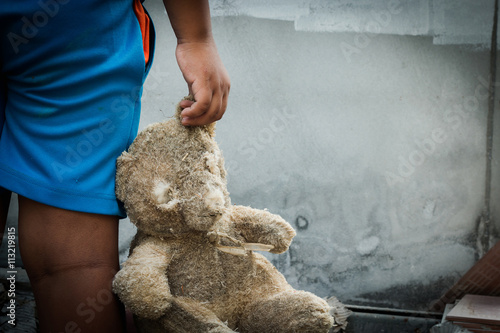 Fotografija  Poor child holding a teddy bear