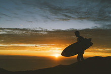 Silhouette Of Man With Surfboard On Mountain Peak