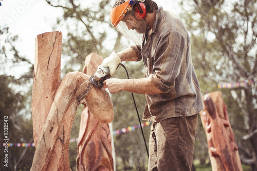 Man carving wood with grinder - 113225412
