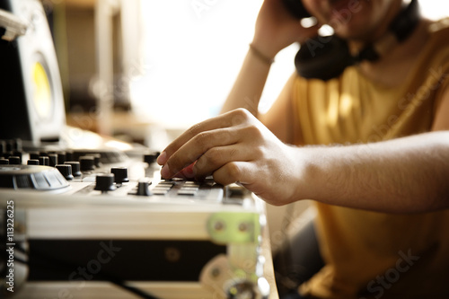 Cropped image of DJ playing sound mixer at recording studio Poster