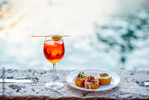 Photographie Spritz Aperol drink with venetian traditional snacks cicchetti on the water chanal background in Venice