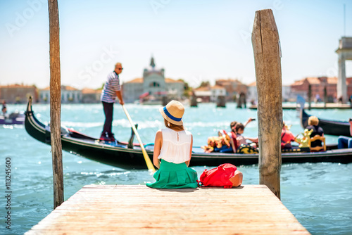 Young female traveler sitting on the pier and enjoying beautiful view on venetian chanal with gondolas floating in Venice
