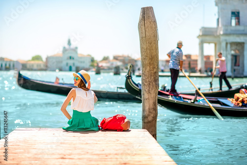 Stickers pour porte Venise Young female traveler sitting on the pier and enjoying beautiful view on venetian chanal with gondolas floating in Venice