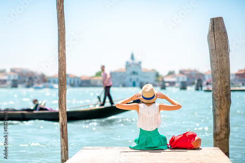Stickers pour portes Venise Young female traveler sitting on the pier and enjoying beautiful view on venetian chanal with gondolas floating in Venice