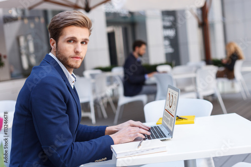 Fototapety, obrazy: Cheerful man is working on computer in restaurant