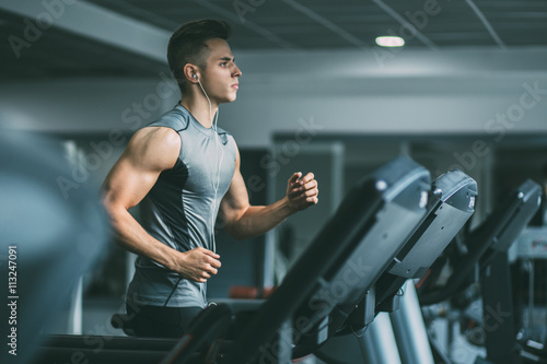 Fotografia Young man in sportswear running on treadmill at gym