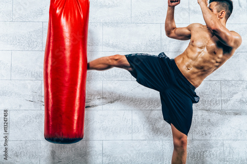 Leinwand Poster Young man kickboxing workout