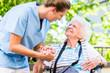 canvas print picture - Altenpflegerin gibt Seniorin Glas Wasser zu trinken