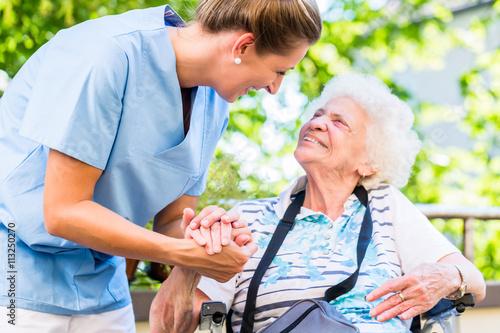 Foto Altenpflegerin gibt Seniorin Glas Wasser zu trinken