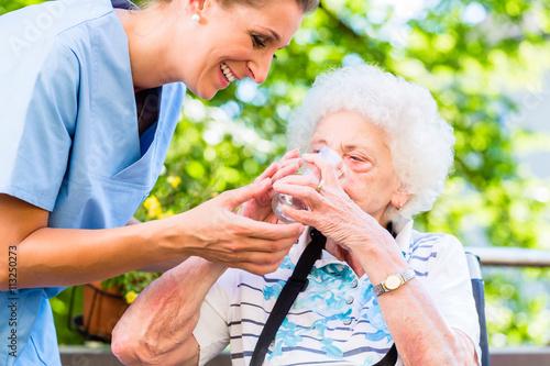 Fotografie, Obraz  Altenpflegerin gibt Seniorin Glas Wasser zu trinken