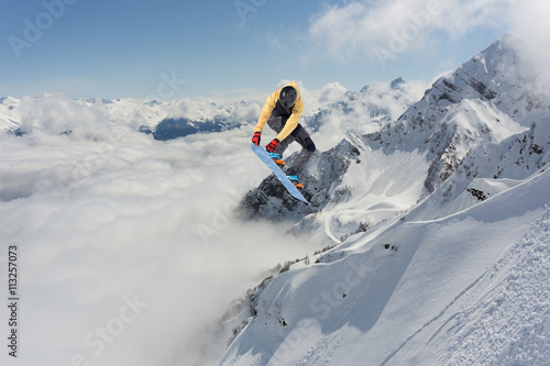 Fotografia Snowboard rider jumping on mountains. Extreme freeride sport.