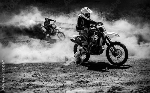 obraz lub plakat Motocross racer accelerating in dust track, Black and white photo