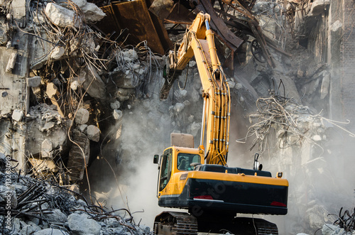 Photo Excavator working at the demolition of an old industrial buildin