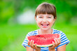 canvas print picture - Child eating watermelon. Kids eat fruits in the garden. Pre teen girl in the garden holding a slice of water melon. happy girl kid eating watermelon. Girl kid with gasses and teeth braces.
