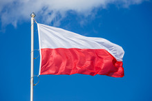 Polish Flag On Blue Sky Backgr...