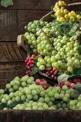 Fototapeta Toskania Bunch of Colorful Grapes in Wodden Basket on Shelf