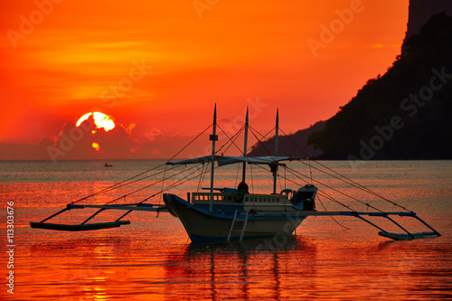 Garden Poster Red Traditional filippino boat at El Nido bay in sunset lights.