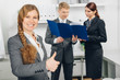 business woman working in office shows thumb up
