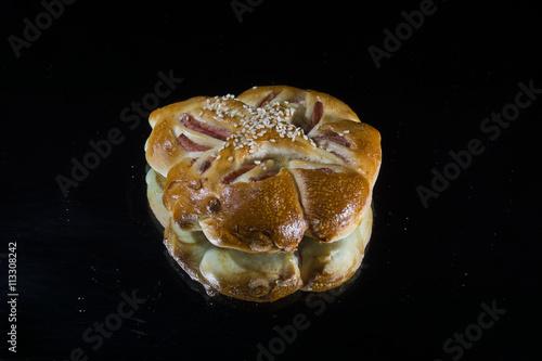 Fotografía  Булочка с запечённой колбасой на тёмном фоне.
