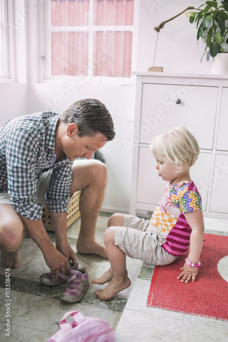 Father assisting daughter in putting shoes at home Poster