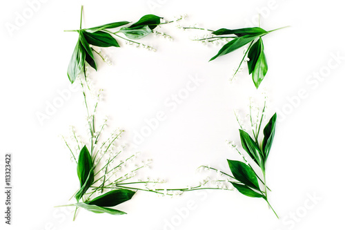 Wall Murals Lily of the valley wreath frame with lily of the valley, branches and leaves isolated on white background. flat lay, overhead view