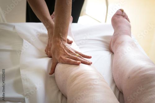 Terapista che esegue il massaggio linfodrenante  manuale su gambe con problemi d Canvas-taulu