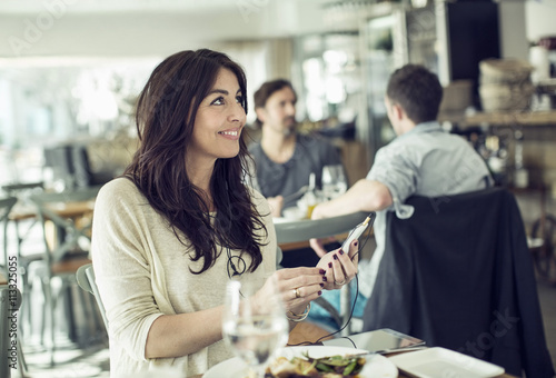 Foto op Canvas Restaurant Smiling businesswoman holding mobile phone in restaurant