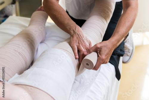 Fotografia  Terapista che esegue il bendaggio  elastocompressivo su arti inferiori con probl