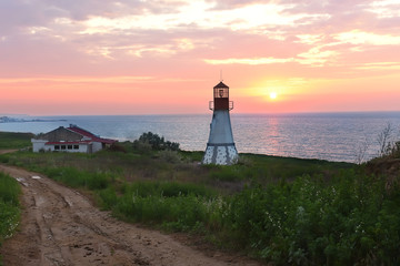 FototapetaLighthouse on the coast. beautiful sunrise, the sun is above the horizon, green vegetation around the lighthouse. Dark