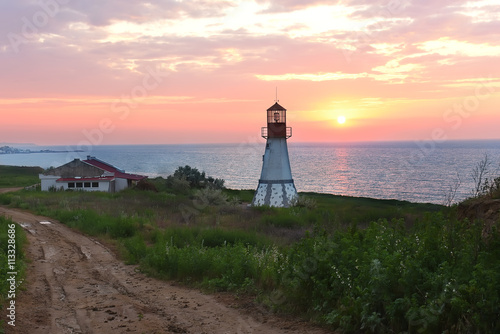 Lighthouse on the coast. beautiful sunrise, the sun is above the horizon, green vegetation around the lighthouse. Dark