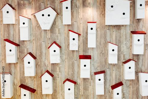 Fototapeta Birdhouses on the wall. Neighborhood and property concept