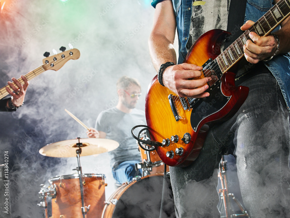 Fototapety, obrazy: Rock band performs on stage. Guitarist, bass guitar and drums. Guitarist in the foreground. Close-up.