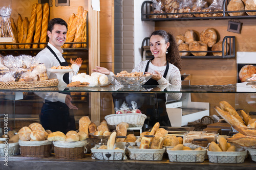 Foto op Canvas Bakkerij Young happy couple selling pastry and loaves