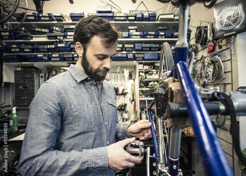 Mid adult repairman repairing bicycle at workshop