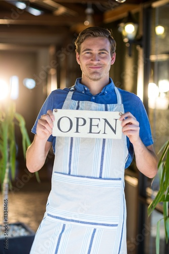 Portrait of smiling chef holding open sign Slika na platnu