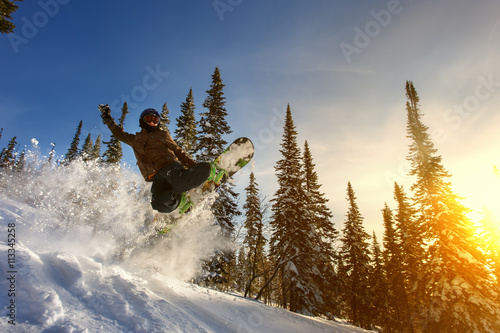 Jumping snowboarder on snowboard in mountains in ski resort Wallpaper Mural