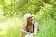 Frau sitzt im Gras.
