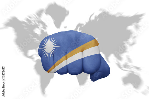fist with the national flag of Marshall Islands on a world map ...